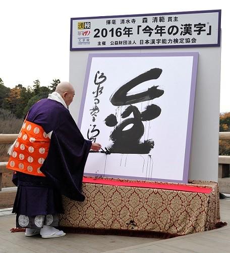 今年の漢字「金」を揮毫(きごう)する森清範貫主