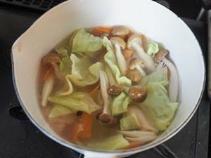 鶏むね肉やキャベツなどの具材を切り、鍋に水を入れて、中火で4分煮込む