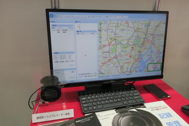 写真左は通信型ドライブレコーダーソリューションの概要がまとめられたパネル。写真右の左側に映っているデバイスは通信機能が内蔵されたドライブレコーダー。モニターに映し出されている画面は「docoですcar Safety」や「docoですcar NEXT」で見える化された情報が表示されたもの